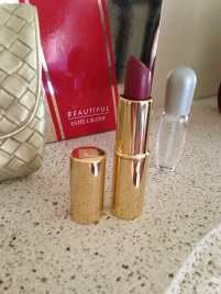 includes gold clutch, pleasure perfume, and pure color passion fruit shimmer lip stick